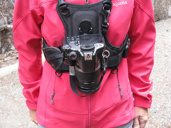 Camera is securely locked in place, with a safety strap, but is instantly accessible.  No more swinging camera!