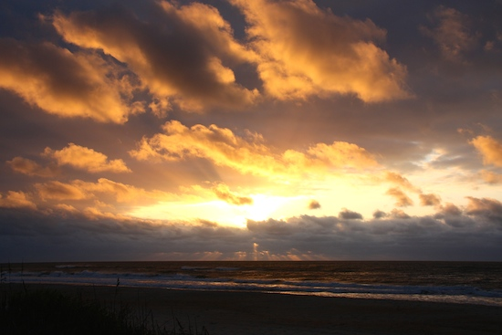 Watch the sun rise from the sand dunes over the beach.