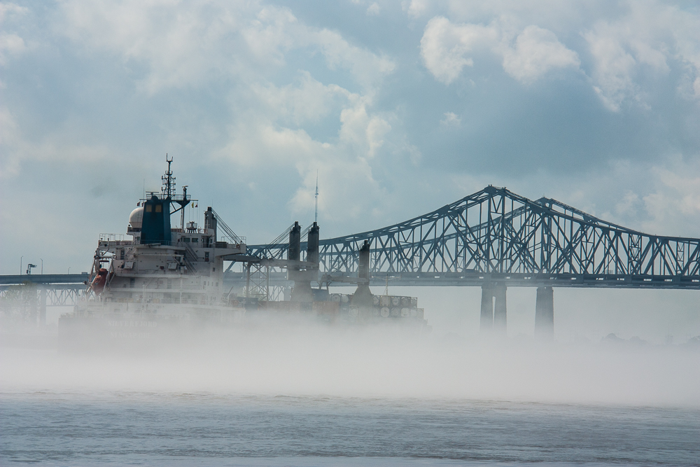 A ship transits the muddy meandering Mississippi in the fog.